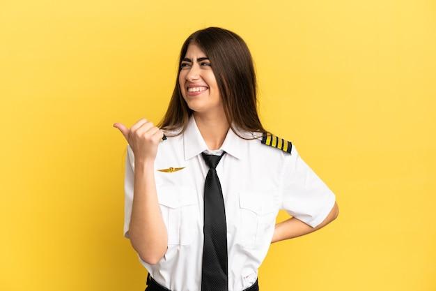 Flugzeugpilot isoliert auf gelbem hintergrund, der zur seite zeigt, um ein produkt zu präsentieren