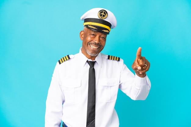 Flugzeugpilot senior mann isoliert auf blauem hintergrund überrascht und zeigt nach vorne