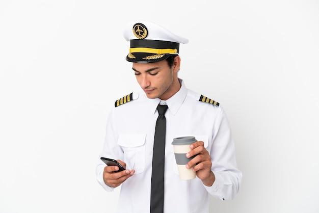 Flugzeugpilot über isoliertem weißem hintergrund mit kaffee zum mitnehmen und einem handy