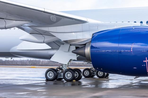 Flugzeugseitenansicht am flughafen zeigt fahrwerk, unter flügel und motor.