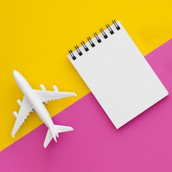 Flugzeugspielzeug und -notizbuch auf tablec