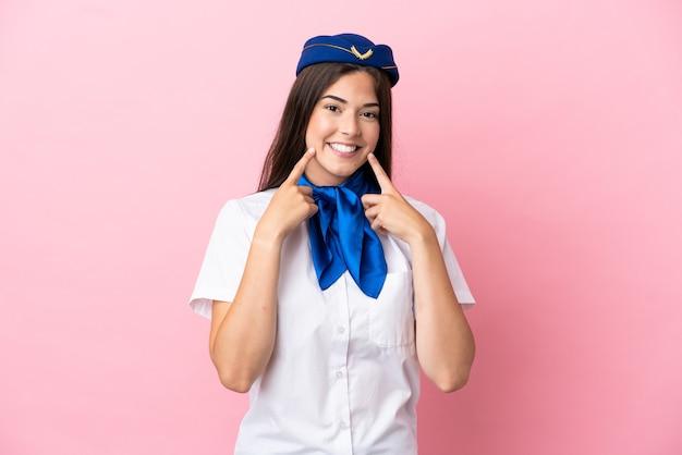 Flugzeugstewardess brasilianerin isoliert auf rosa hintergrund lächelnd mit einem glücklichen und angenehmen ausdruck