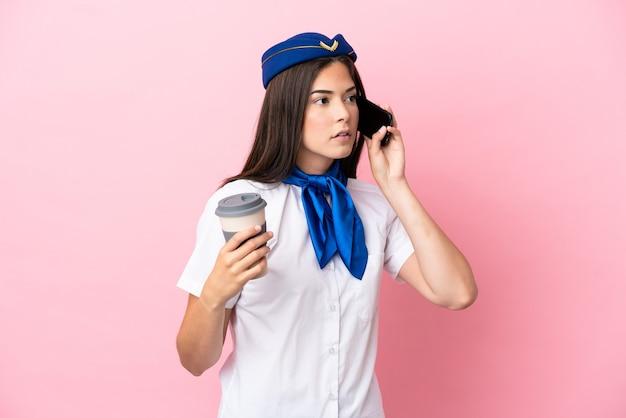 Flugzeugstewardess brasilianerin isoliert auf rosa hintergrund mit kaffee zum mitnehmen und einem handy