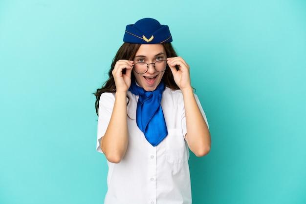 Flugzeugstewardess frau auf blauem hintergrund mit brille isoliert und überrascht
