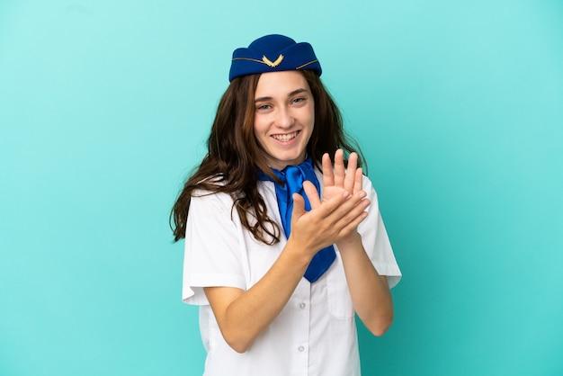 Flugzeugstewardess frau isoliert auf blauem hintergrund applaudieren nach präsentation in einer konferenz