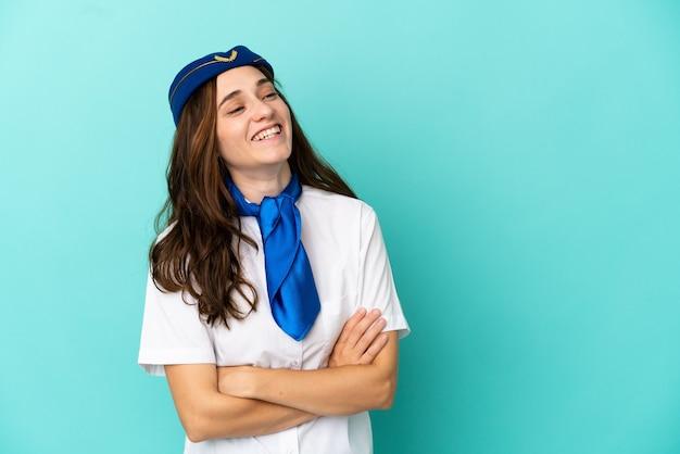 Flugzeugstewardess frau isoliert auf blauem hintergrund glücklich und lächelnd