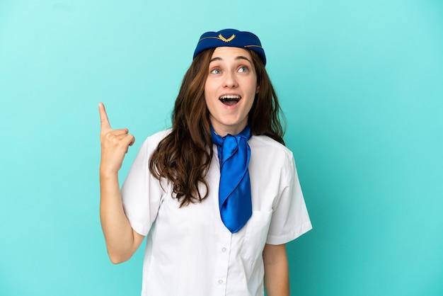 Flugzeugstewardess frau isoliert auf blauem hintergrund nach oben zeigend und überrascht