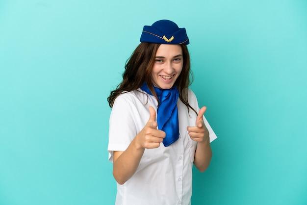 Flugzeugstewardess frau isoliert auf blauem hintergrund nach vorne zeigend und lächelnd