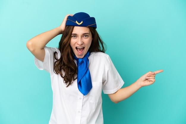Flugzeugstewardess frau isoliert auf blauem hintergrund überrascht und zeigt mit dem finger zur seite