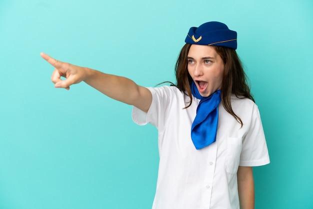 Flugzeugstewardess frau isoliert auf blauem hintergrund wegweisend