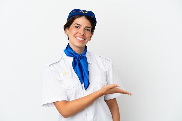 Flugzeugstewardess kaukasische frau isoliert auf weißem hintergrund, die eine idee präsentiert, während sie lächelnd in richtung blickt