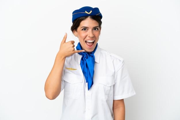 Flugzeugstewardess kaukasische frau isoliert auf weißem hintergrund, die telefongeste macht. ruf mich zurück zeichen