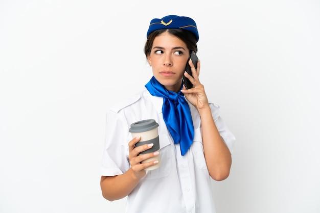 Flugzeugstewardess kaukasische frau isoliert auf weißem hintergrund mit kaffee zum mitnehmen und einem handy