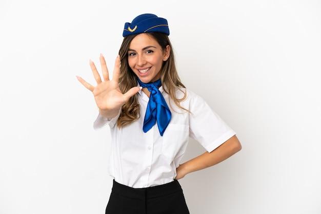 Flugzeugstewardess über isoliertem weißem hintergrund, der mit den fingern fünf zählt