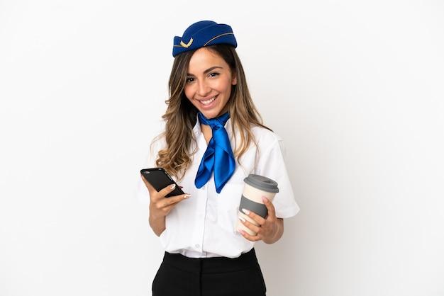 Flugzeugstewardess über isoliertem weißem hintergrund mit kaffee zum mitnehmen und einem handy