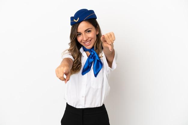 Flugzeugstewardess über isoliertem weißem hintergrund zeigt mit dem finger auf sie, während sie lächelt