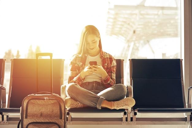 Flugzeugverkehrkonzept mit der jungen zufälligen frau, die mit handgepäckkoffer sitzt. flughafenfrau am telefon am tor, das in anschluss wartet.