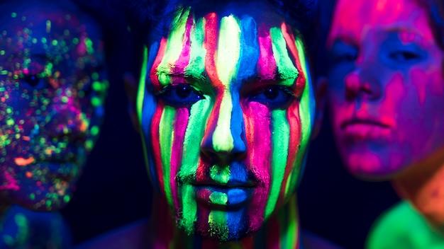 Fluoreszierendes make-up auf den gesichtern der menschen