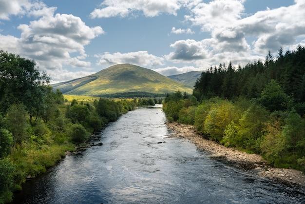 Fluss, der durch die bäume und berge in schottland fließt