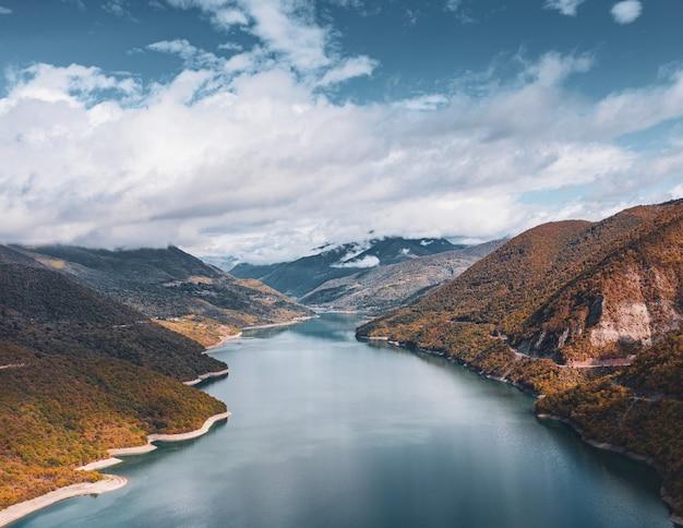 Fluss, der durch die hügel unter dem atemberaubenden bewölkten himmel geht