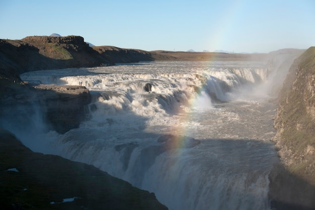 Fluss, der über die felsen schaffen wasserfall und regenbogen fließt