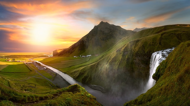 Fluss, der von einem wasserfall in island abfließt, umgeben von bergen bei sonnenuntergang