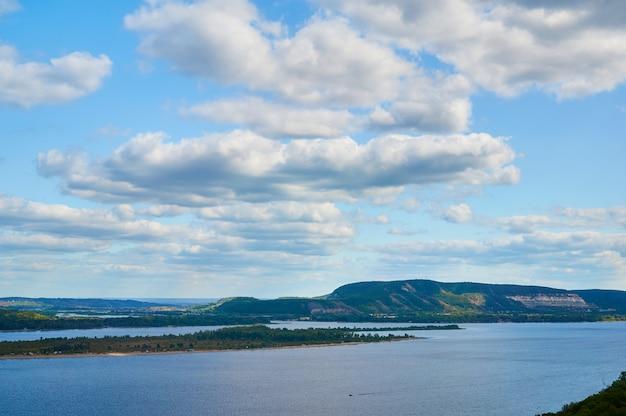 Fluss gegen den blauen himmel mit wolken und wäldern.