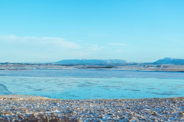Fluss in der ebene in island. die ufer sind mit schnee bedeckt. winterlandschaft, freiflächen.