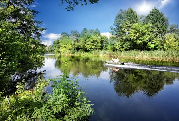 Fluss mit einem motorboot und grünen bäumen am ufer