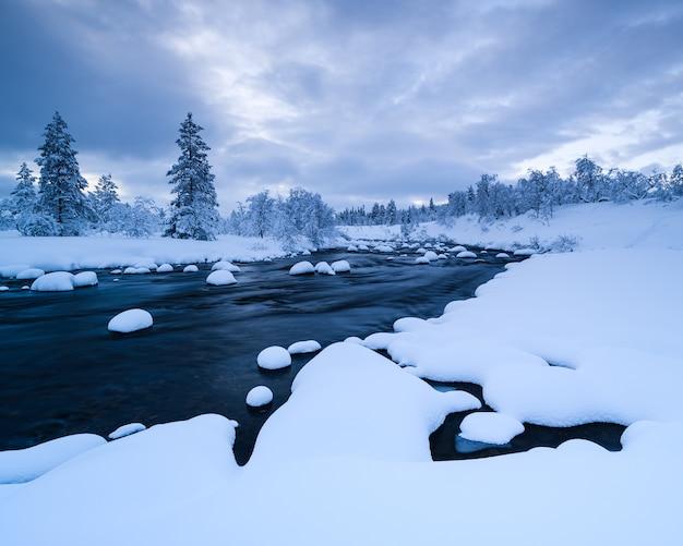 Fluss mit schnee und ein wald in der nähe mit schnee im winter in schweden bedeckt