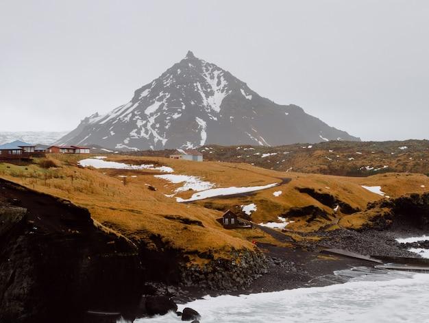 Fluss umgeben von felsen und hügeln bedeckt mit schnee und gras in einem dorf in island