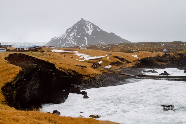 Fluss umgeben von hügeln mit viel grün und schnee in einem dorf in island