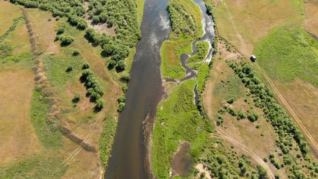 Fluss umgeben von wiesen und bäumen
