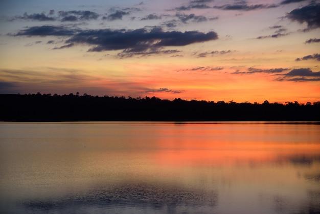 Fluss und berg im sonnenuntergang auf blauem und orange himmelhintergrund der nacht