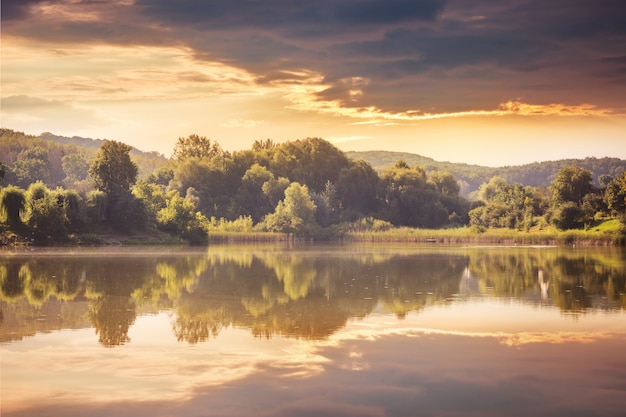 Fluss und wald bei sonnenuntergang. zeigen sie bäume und wolken im wasser des sees an