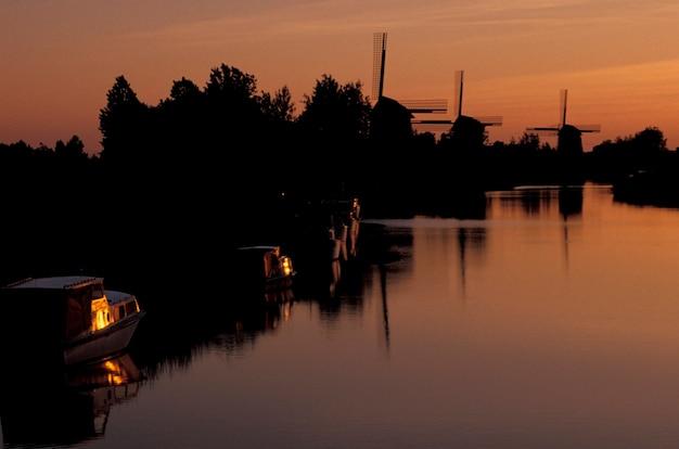 Fluss und windmühlen bei sonnenuntergang, holland