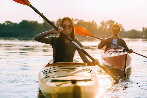 Flussabenteuer genießen. schönes junges paar, das zusammen auf dem fluss kajak fährt und lächelt