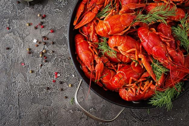 Flusskrebs. rot gekochte langusten auf tisch im rustikalen stil, nahaufnahme. hummer nahaufnahme. randgestaltung. draufsicht. flach liegen.