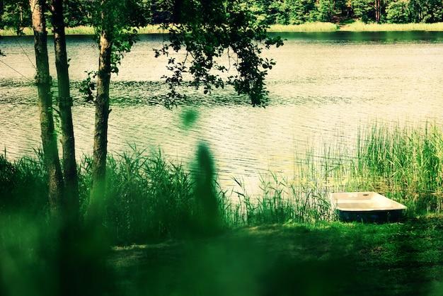 Flusslandschaft, baum, boot. reine natur hintergrund. sommer-konzept
