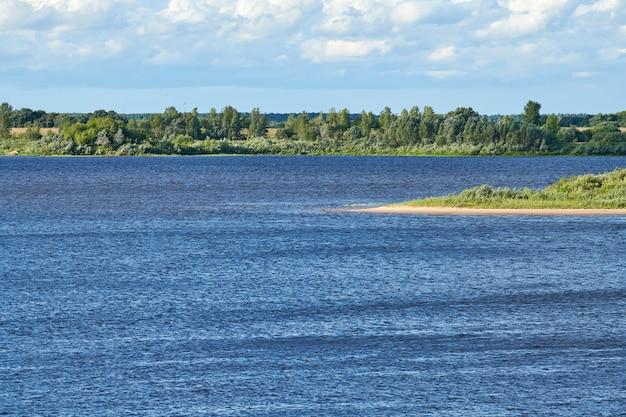 Flusslandschaft. blaues tiefes wasser mit schneller strömung. grüne dickichte an der anderen küste.