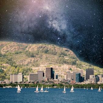 Flussufer mit blick auf sternhaufen hinter dem berg collage mit kosmos- und astronomie-thema