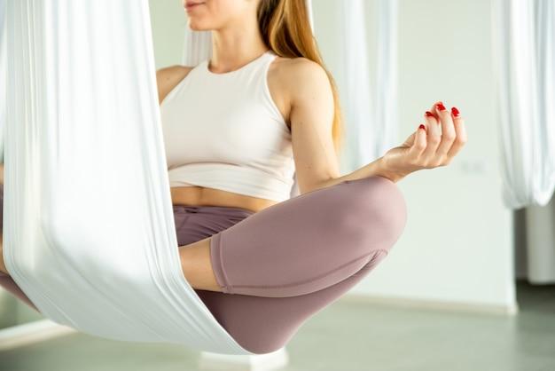 Fly yoga ein mädchen sitzt im lotussitz in einer hängematte für aerial yoga entspannung in yoga-kursen