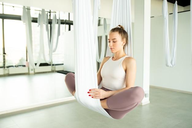 Fly yoga ein mädchen sitzt im lotussitz in einer roten hängematte für aerial yoga und macht mudras