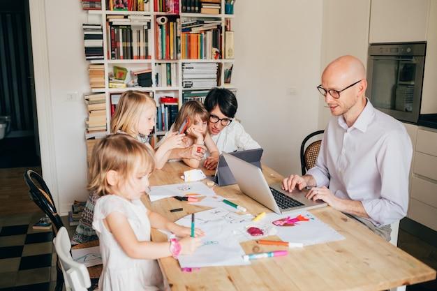 Fmaily indoor-sitztisch, der aktivitäten ausführt - mit smartphone, tablet, computer - technologie, zusammengehörigkeit, aktivitätskonzept