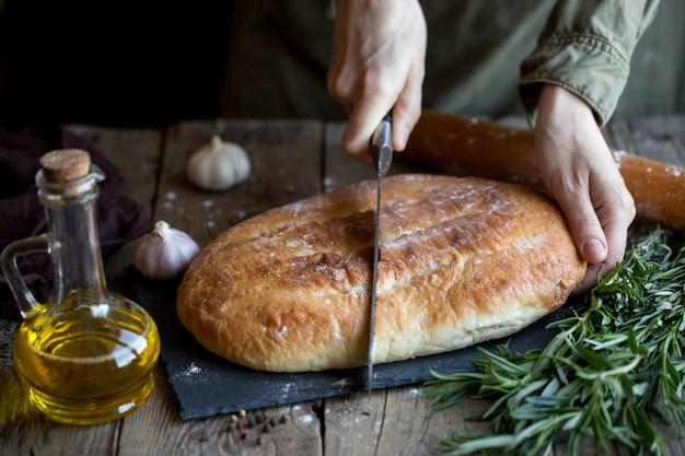 Focaccia mit butter und salz. focaccia auf einem schneidebrett mit kräutern und gewürzen.