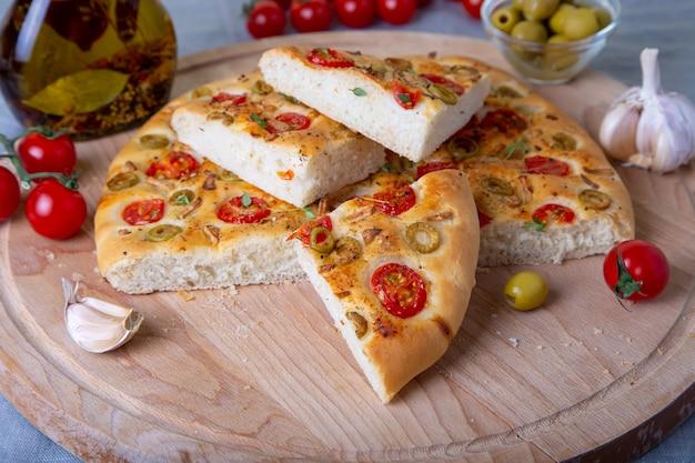 Focaccia mit tomaten und oliven. traditionelles italienisches brot. hausgemachtes backen. nahaufnahme, selektiver fokus.