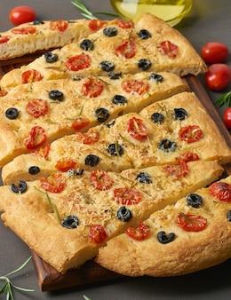 Focaccia, pizza, fladenbrot mit tomaten, oliven und rosmarin auf dunkelbraunem tisch,