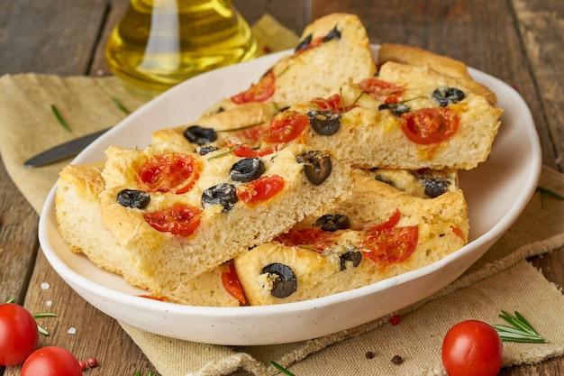 Focaccia, pizza in der platte mit tomaten, oliven und rosmarin. gehacktes italienisches fladenbrot.