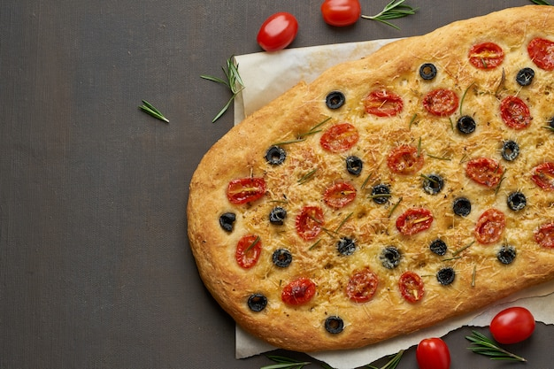Focaccia, pizza, italienisches fladenbrot mit tomaten, oliven und rosmarin auf brauner tabelle