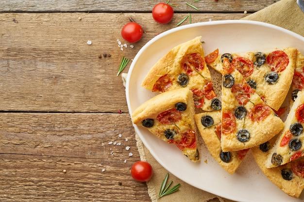 Focaccia, pizza, scheiben des italienischen fladenbrotes mit tomaten, oliven und rosmarin auf hölzernem